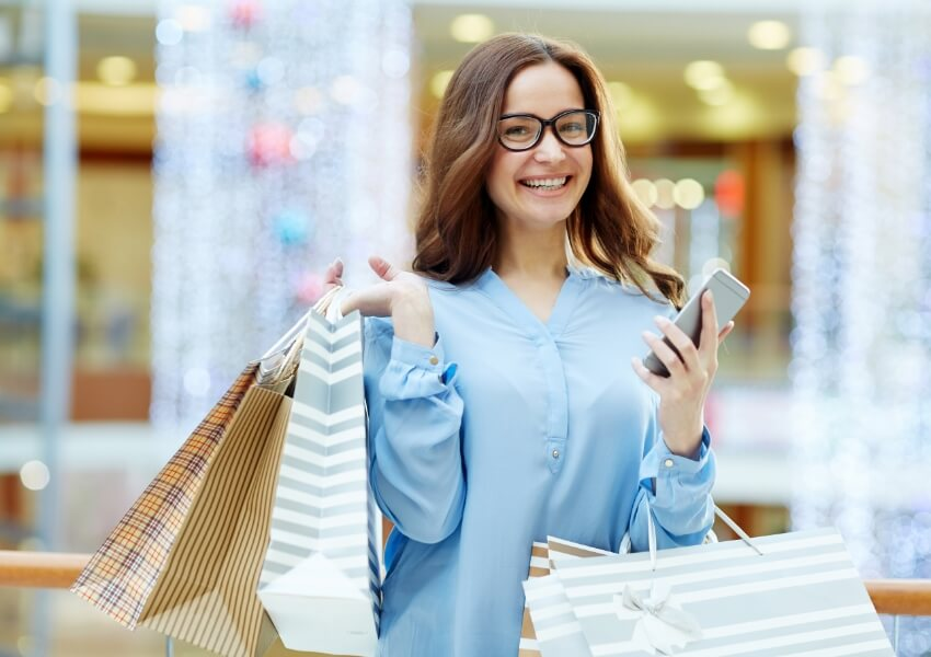 Laughing shopper with smartphone and bags looking at camera
