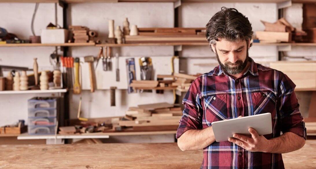 Hombre en taller de carpintería con tablet entre las manos